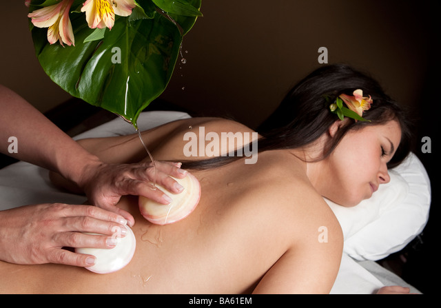 A young adult woman receives a massage with shells - Stock Image