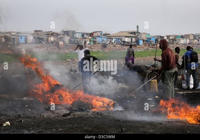 Teenage boys burn cables from computers and other electronics to recover copper near the Agbogbloshie slum in Accra, - Stock Image