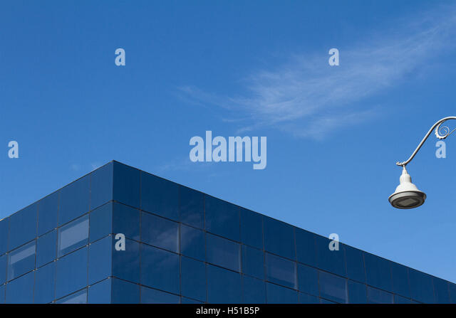 Minimalist photo of a glass office city building detail against a blue sky and a white street light - Stock Image