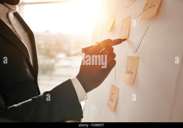 Cropped shot of businessman putting his ideas on white board during a presentation in conference room. Focus in - Stock-Bilder