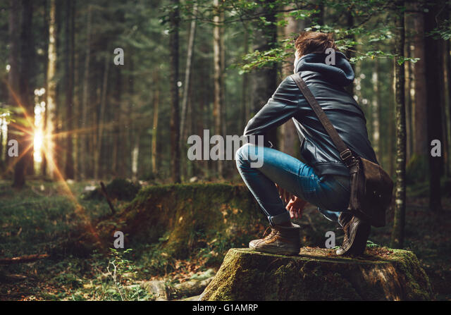 Young handsome man exploring the forest and looking around, nature and freedom concept - Stock-Bilder
