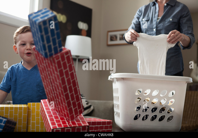 Mother sorting laundry, son playing - Stock-Bilder