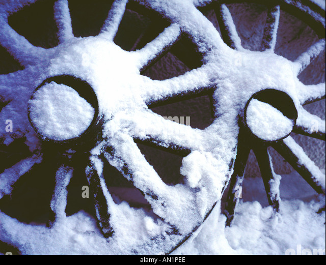 old wooden wagon wheels covered by snow. Photo by Willy Matheisl - Stock Image