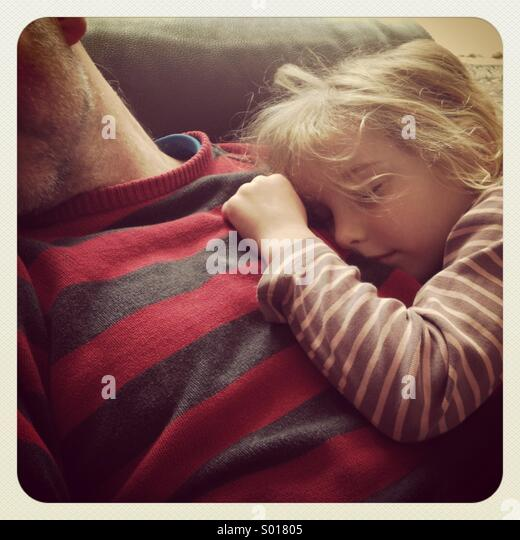 A daughter asleep on her father's chest - Stock Image