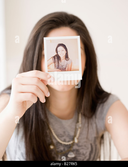 Woman holding photograph in front of face - Stock Image