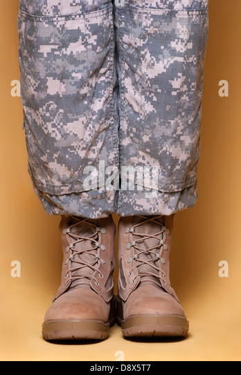Army combat camouflage uniform pants (ACU) and tan desert combat boots. - Stock Image