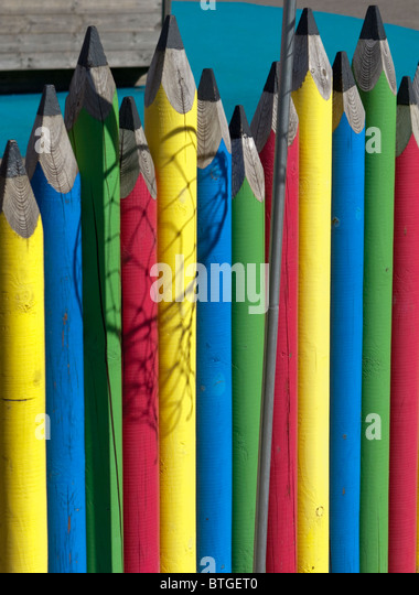 A fence in a school playground in the form of giant coloured pencils with the shadow of a netball net falling across - Stock Image