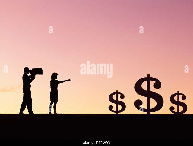 Conceptual of a couple looking at dollar signs in field near Winnipeg, Manitoba, Canada - Stock Image