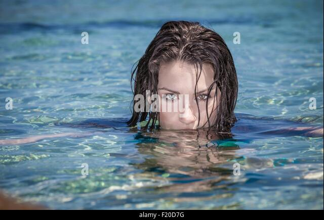 Portrait of beautiful young woman with face submerged in sea - Stock Image