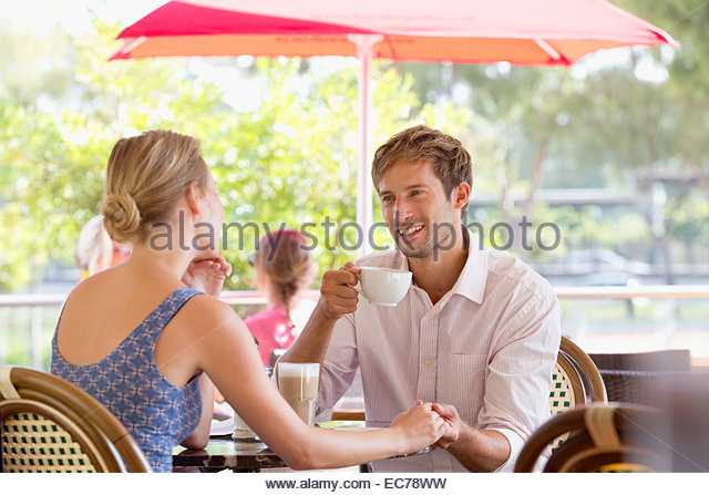 Couple talking at outdoor cafe - Stock-Bilder