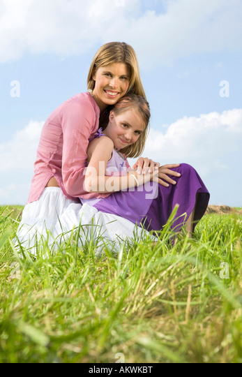 Mother and daughter, crouching - Stock Image