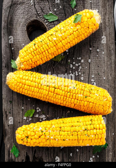 Delicious grilled corn on a wooden board - Stock Image