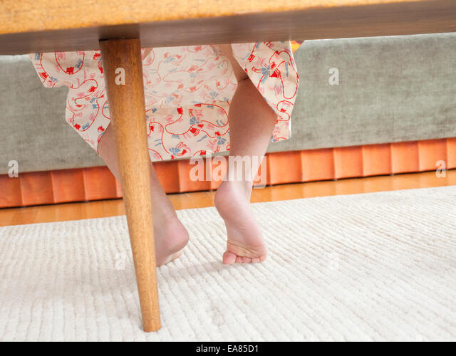 feet of child sitting on table - Stock Image