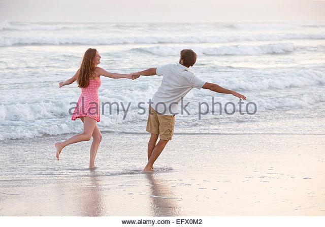 Couple, holding hands, playfully running through waves on sunny beach - Stock-Bilder