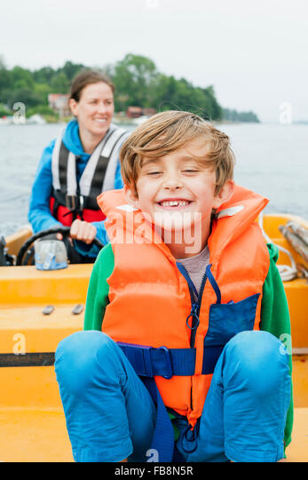 Sweden, Uppland, Runmaro, Barrskar, Portrait of boy (6-7) on motorboat, mother in background - Stock Image