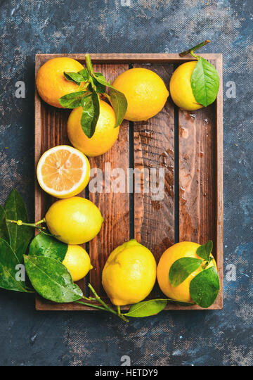 Freshly picked lemons with leaves in wooden tray - Stock Image