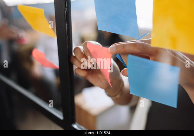 Close up shot of hands of woman sticking adhesive notes on glass wall in office - Stock Image