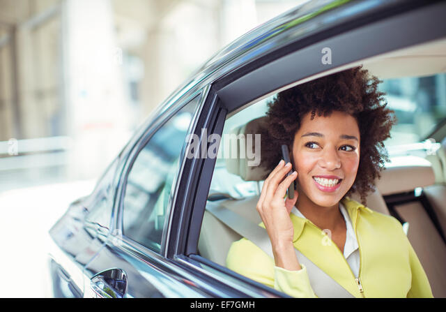 Businesswoman talking on cell phone in back seat of car - Stock Image