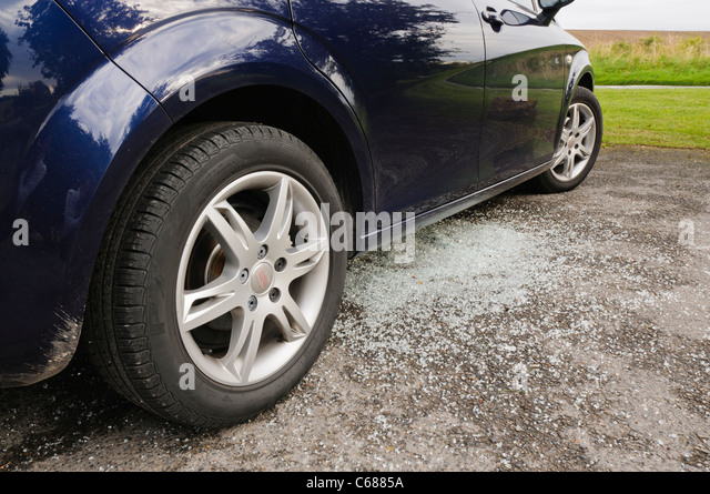 Broken glass underneath a car after its window is smashed by thieves - Stock Image