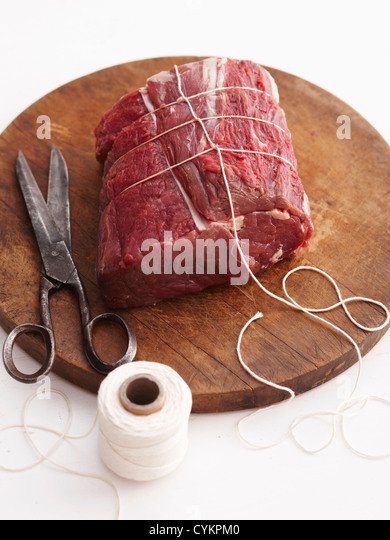 Twine wrapping raw beef - Stock Image