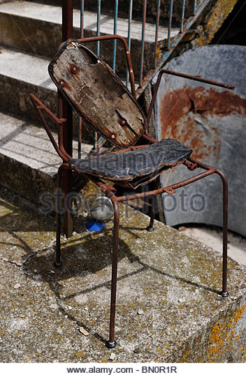 A rusty and decayed dining chair in an Italian farmyard - Stock Image