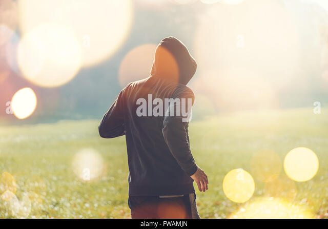 Unrecognizable hooded man jogging outdoors, healthy lifestyle activity in the park in early autumn morning, retro - Stock Image