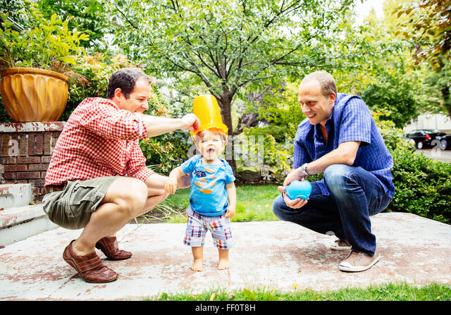 Gay fathers playing with baby son outdoors - Stock Image