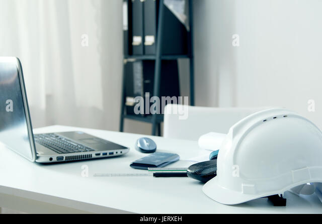 Home office of an architect with white helmet, laptop pc and drawing accessories - Stock Image