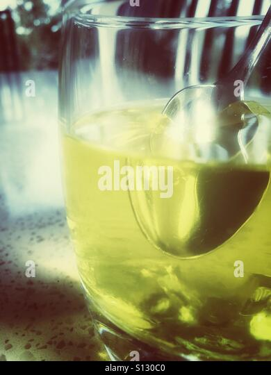 A spoon breaks into a dish of lemon gelatin. - Stock Image