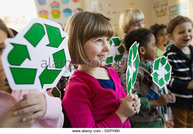 Girl holding recycling symbol in school - Stock Image