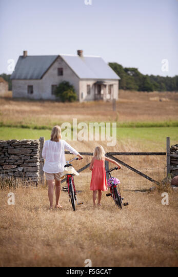Sweden, Gotland, Faro, Mother and daughter (8-9) wheeling bicycles toward farm gate - Stock Image