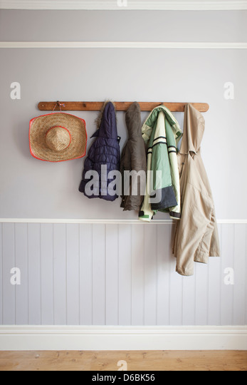 Coats and hat on coat rack - Stock Image
