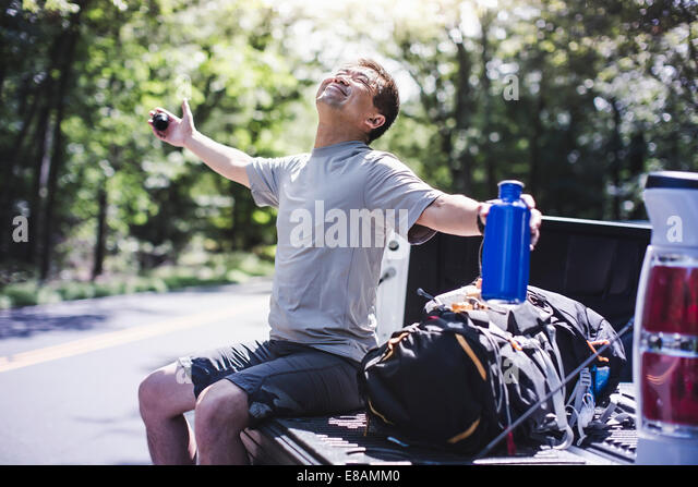 Mature man sitting on pick up truck with arms out - Stock Image