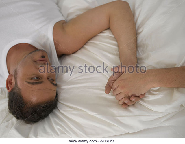 High angle view of a young man lying on the bed - Stock Image