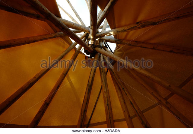 An inside view of a Plains Indian teepee or tipi, looking up at the wooden poles supporting and protruding through - Stock Image