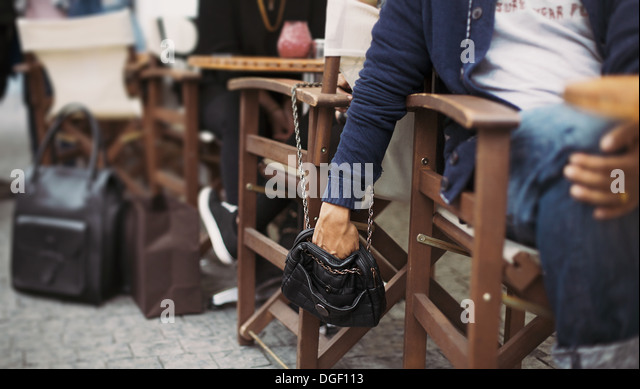 Man stealing wallet from the woman's purse at street cafe during daytime. Pickpocketing at the street cafe - Stock Image