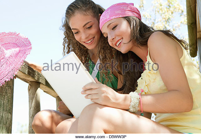 Women using tablet computer on patio - Stock Image