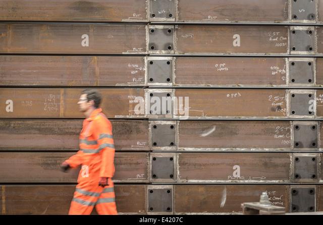 Engineer walking past marine fabrication in factory - Stock-Bilder