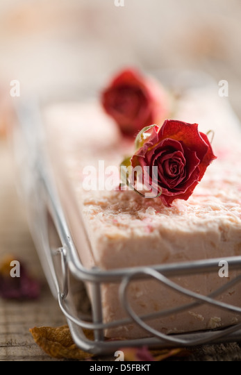 Pink bar of soap with dried roses - Stock Image