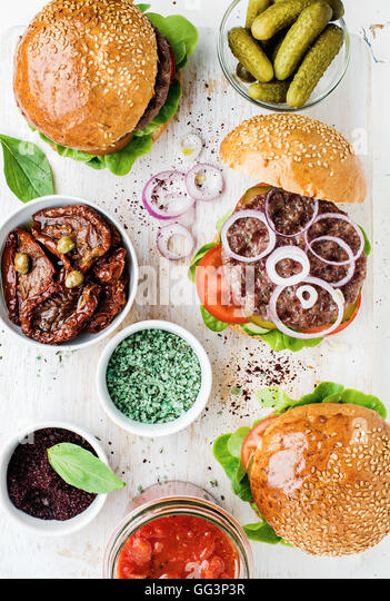 Homemade beef burgers with onion, pickles, vegetables, sun-dried tomatoes, spices - Stock Image