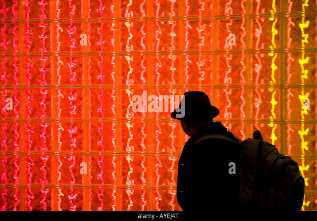 Man walking past a glass block wall lit with red light at Washington Dulles International Airport Washington D C - Stock Image