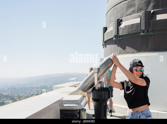 Young woman fooling around with coin binoculars at Griffith Observatory, Los Angeles, California, USA - Stock-Bilder