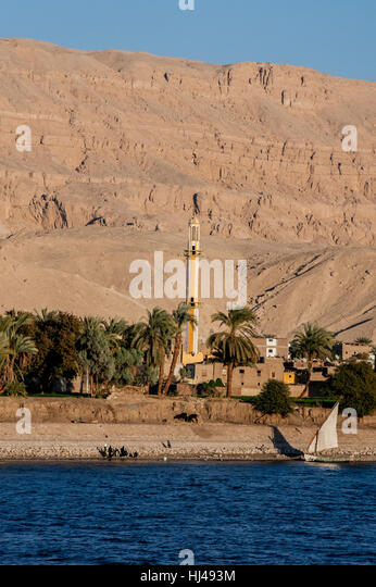 Life along the Nile River, Egypt, with minaret, sailboat and the houses clustered around it. - Stock-Bilder