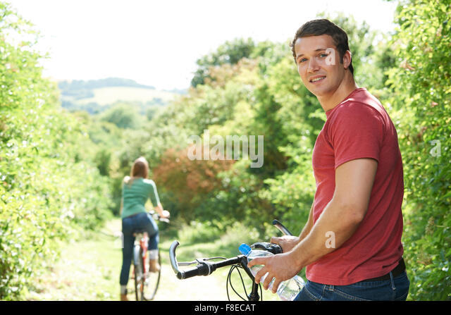 Yoing Couple Cycling In Countryside - Stock Image