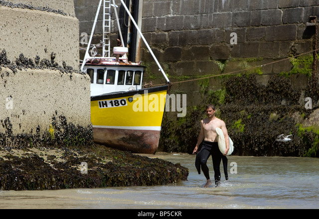 A surfer walks from Newquay Harbour with a yellow fishing boat in the background. - Stock Image