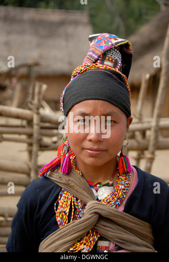 Portrait of young woman of the Akha Loma ethnic group, traditional black costume, colourfully embroidered, cap, - Stock-Bilder