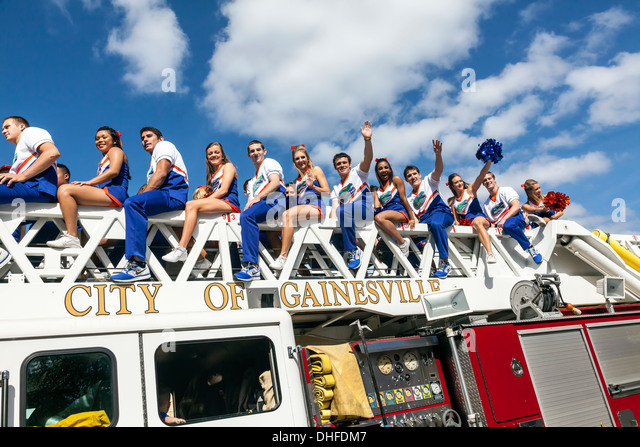 Florida coed cheer leader cheer leading squad riding on a fire truck in the University of Florida Homecoming Parade - Stock Image