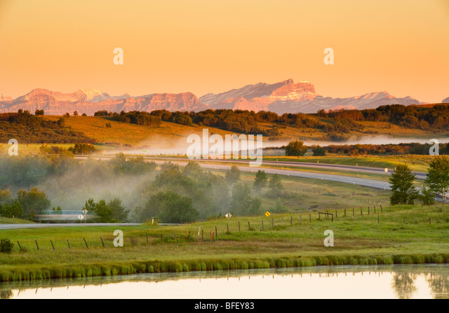 Fog lifting off landscape, Cochrane, Alberta, Canada, trans canada highway, pond, Mountain, Rockies, sunrise - Stock Image