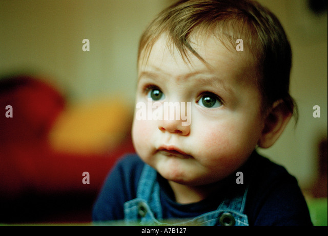 close crop of ruddy faced baby looking worried - Stock Image