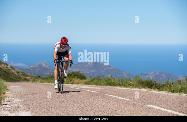Man cycling on road, Corsica, France - Stock Image